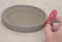 using a silicone rib to smooth pot's walls